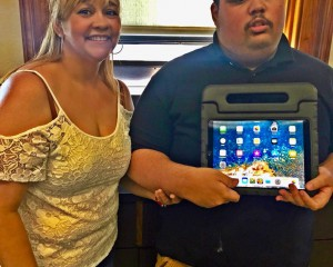 Michael from the SLC Program and his mother show his new iPad provided by a generous grant from the Doug Flutie Jr. Foundation.