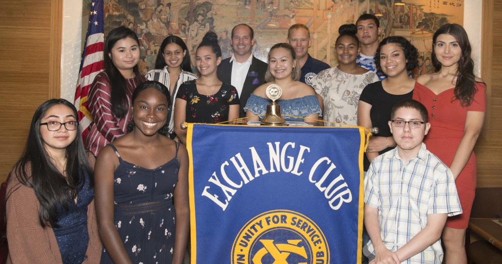student scholarship recipients standing around the Exchange Club banner