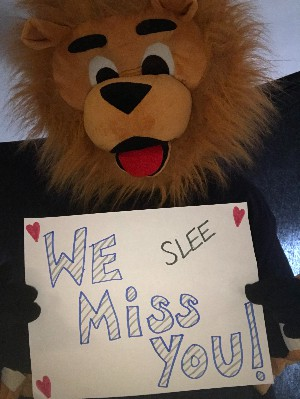 "The mascot Toney holding a ""We Miss You"" sign."