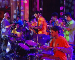 student playing drums and guitar with colorful stage lights