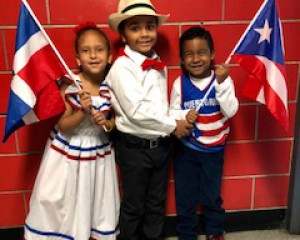 3 kids holding dominican republic and puerto rican flags.