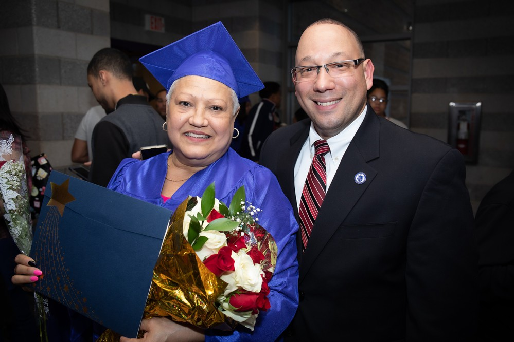 adult graduate in blue robe and man wearing glasses