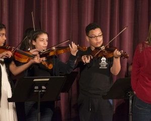 Three students playing the violin with teacher instructing