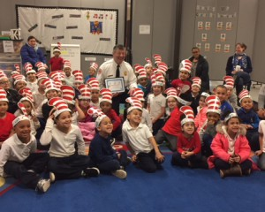 Large group of kids wearing crafted hats sitting around fire chief