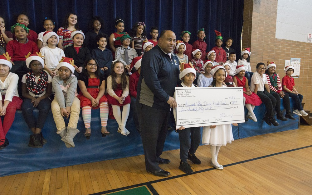 students giving large check to Mayor Rivera