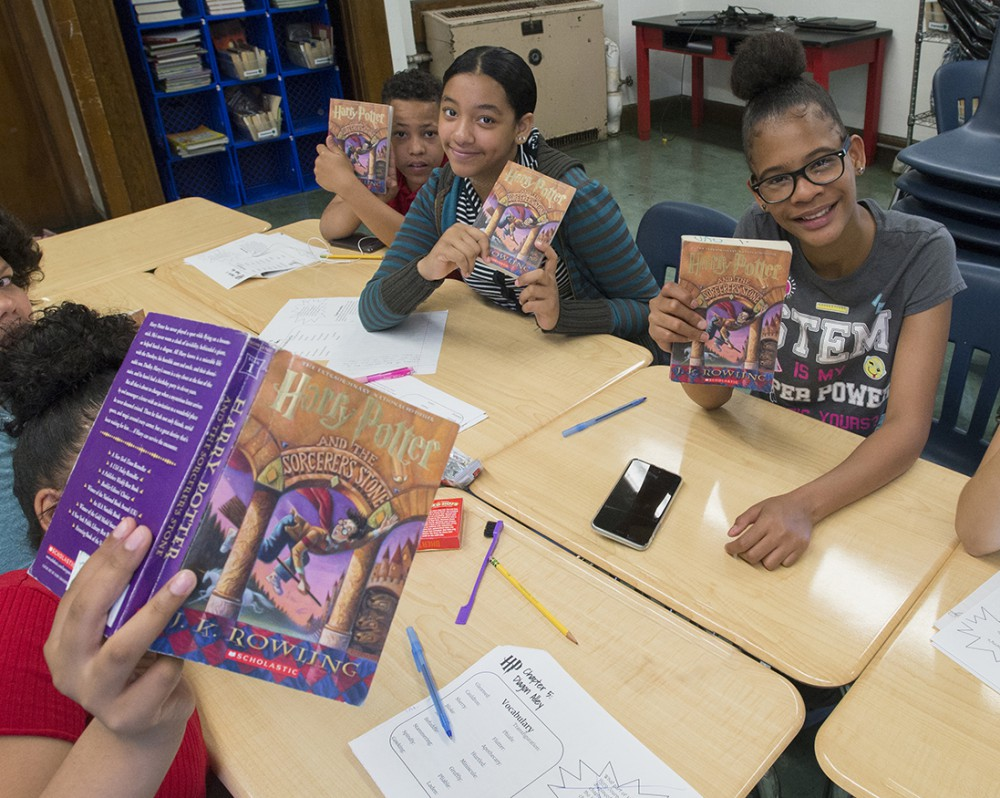 students holding Harry Potter book in classroom