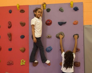 2 Students climbing a colorful rock wall
