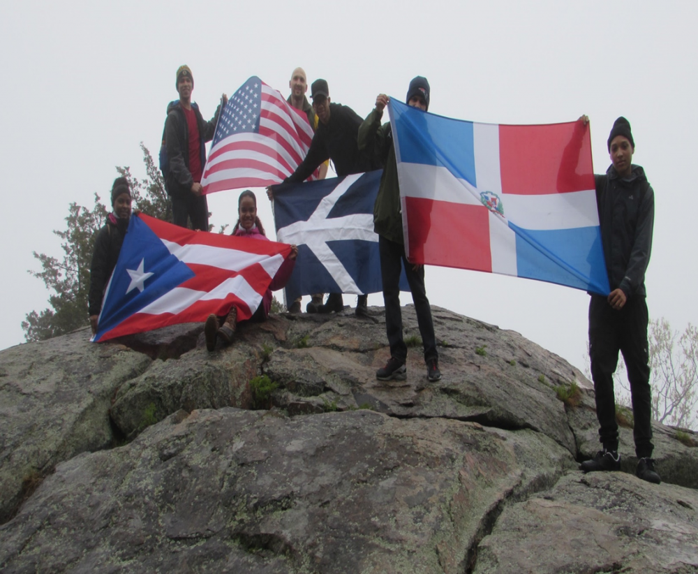 Students holding flags on rocks