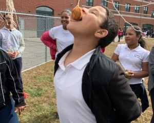 Student grabbing donut on a string with their mouth