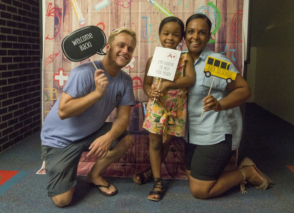 student and 2 teachers in welcome back photo booth
