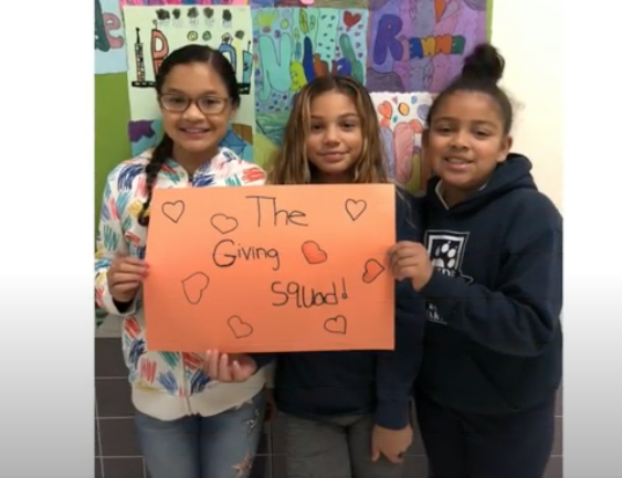 picture of 3 students holding sign