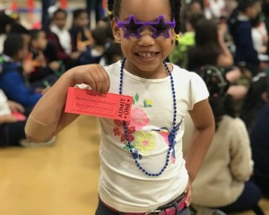 little girl holding ticket to kindness celebration wearing star glasses