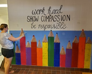 person painting wall mural saying work hard, show compassion, be responsible