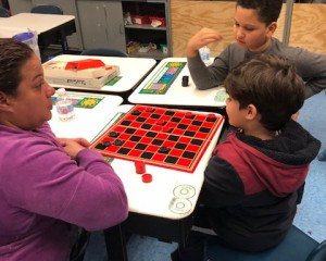 Parent playing checkers with students