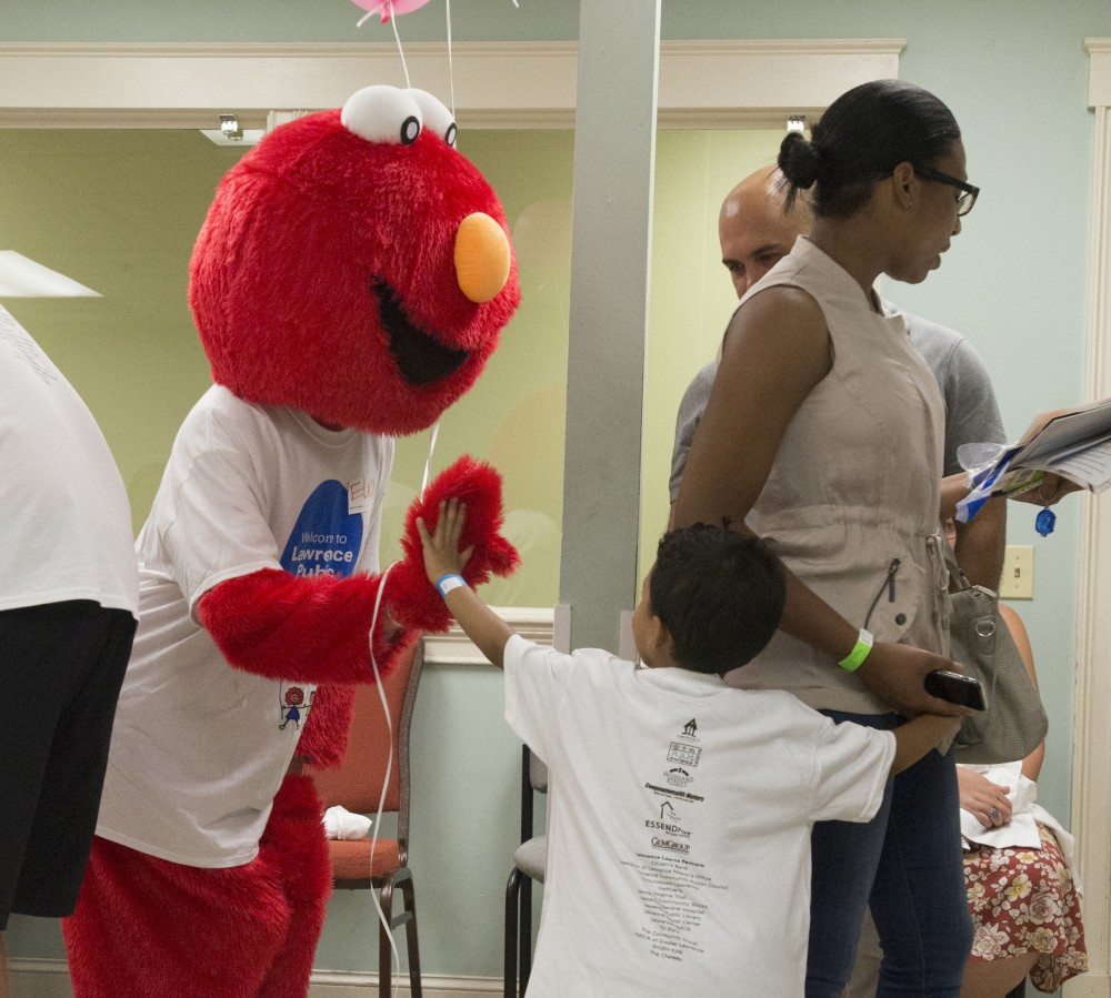 Elmo giving high 5 to a small child