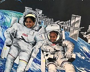 students posing with an astronaut cut out during their field trip