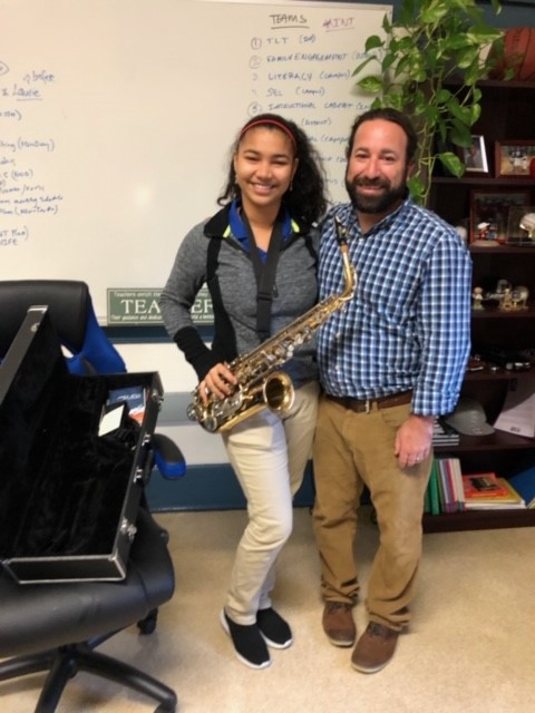 Student with teacher and holding saxophone