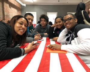 Students sitting at table with red and white table cloth.
