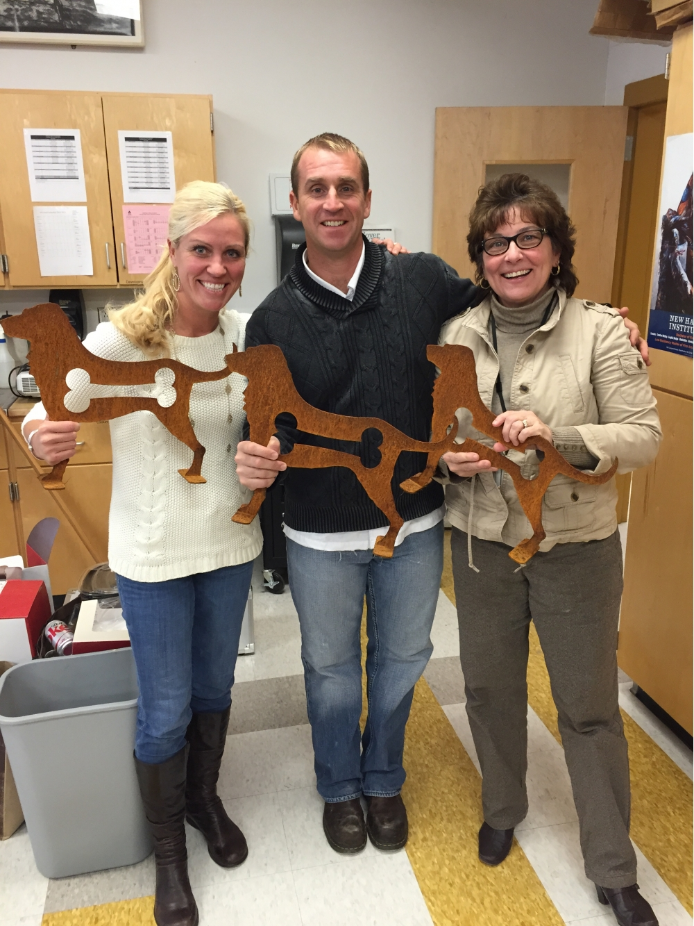 Three people holding metal dog sculpture with a bone cut out of