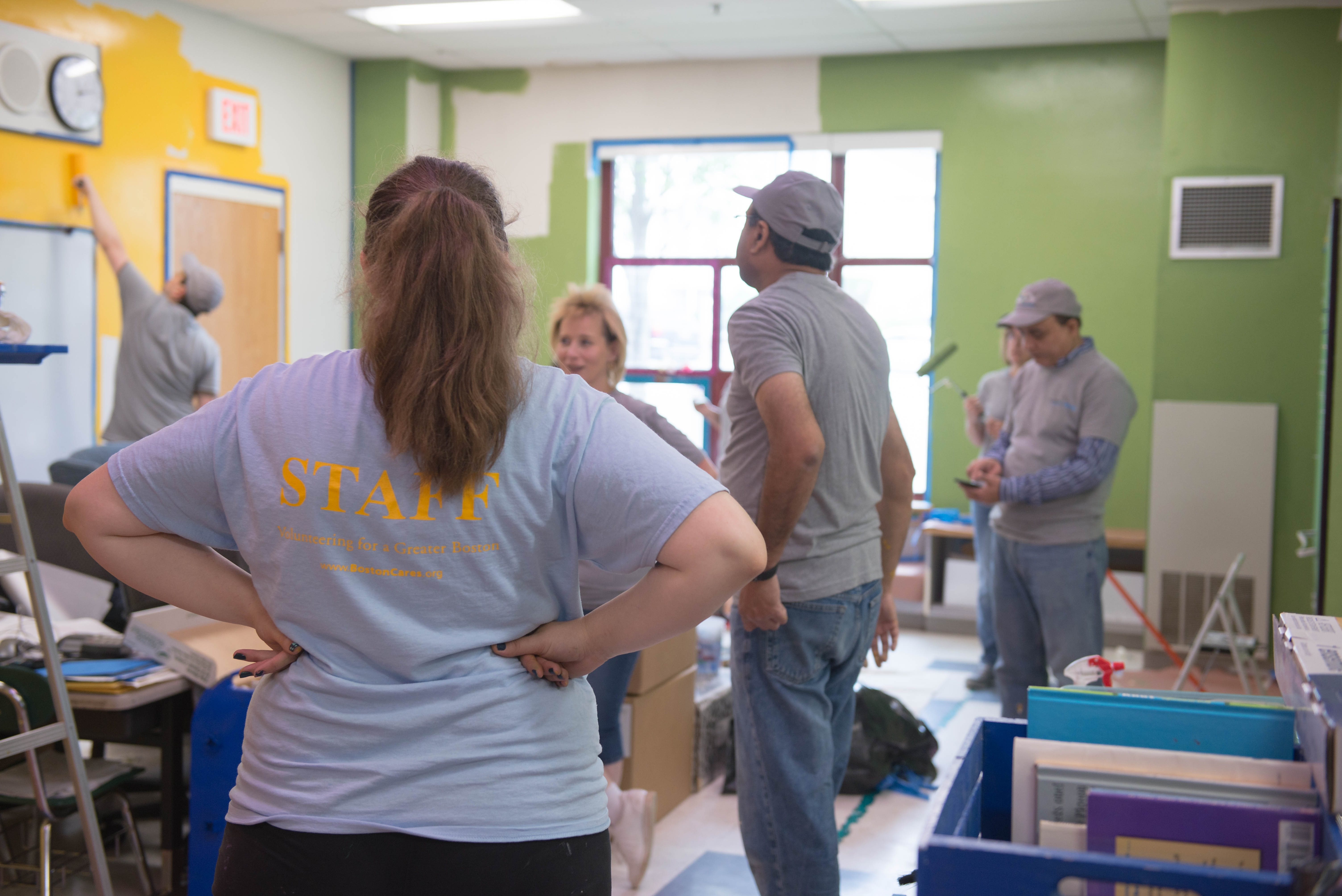 Volunteers painting a classroom yellow and green